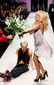 Topless Pamela Anderson and Richie Rich walk on a stage in Auckland, New Zealand